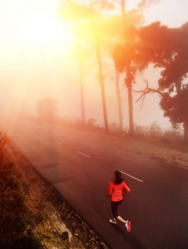 Healthy running runner woman early morning sunrise workout on misty mountain road workout jog. sunflare through the mist gives atmospheric feel and depth to this set of fitness images