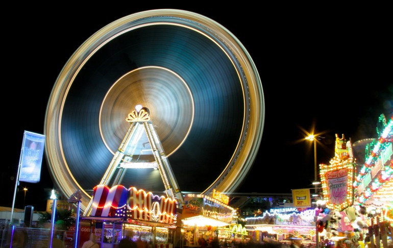 funfair carousel at night with the big merry-go-round wheel
