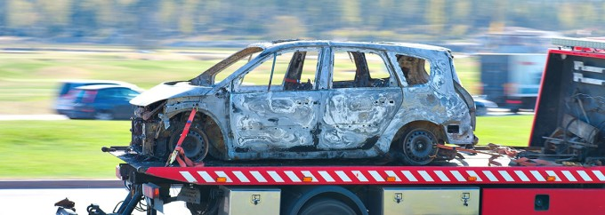Wrecked and burnt car being trnsported by pick up truck