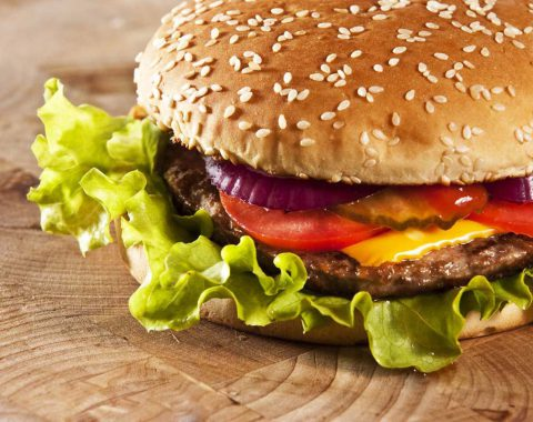 Cheeseburger with onions tomato and ketchup