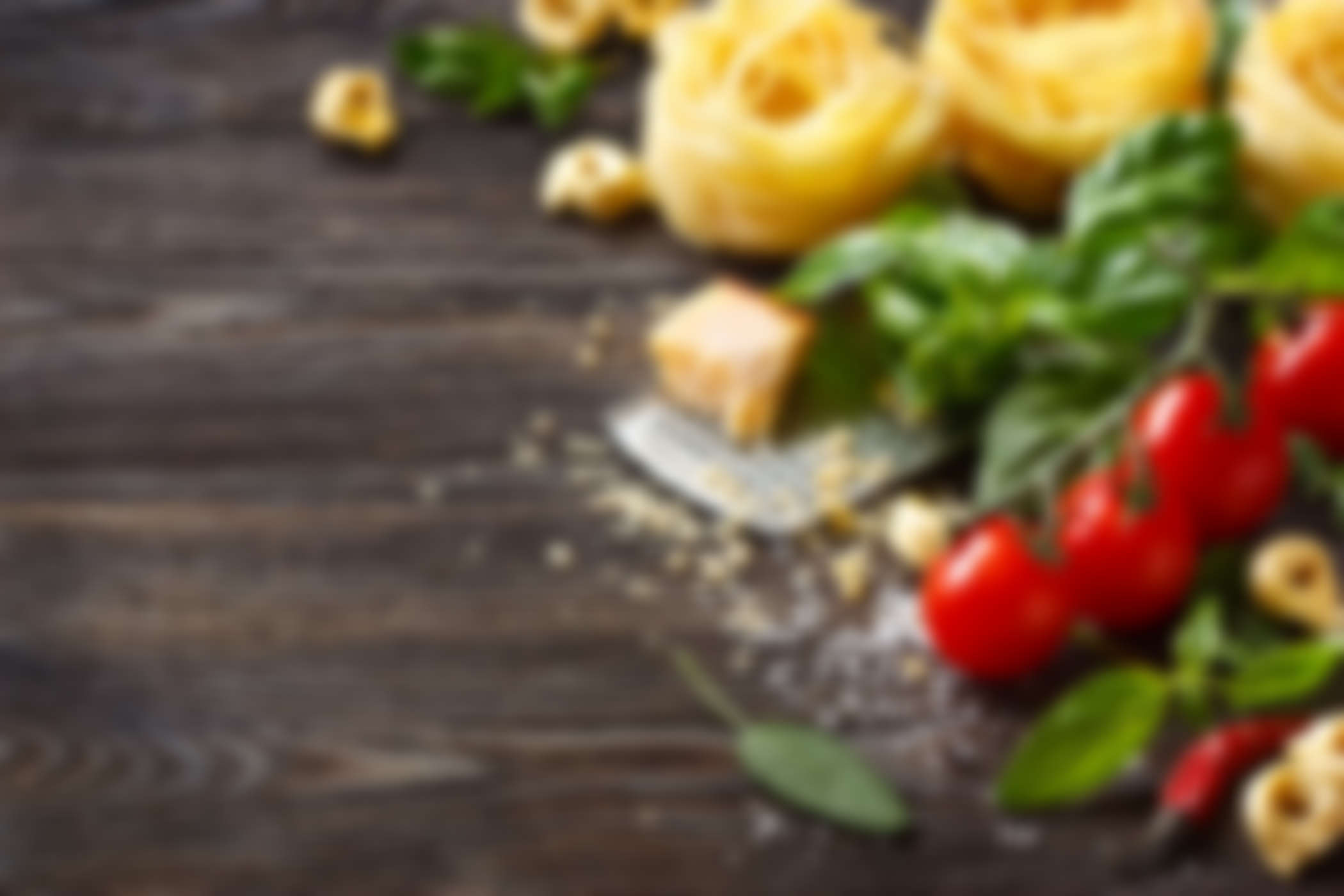 Italian food ingredients for cooking pasta on a wooden background with copy space.