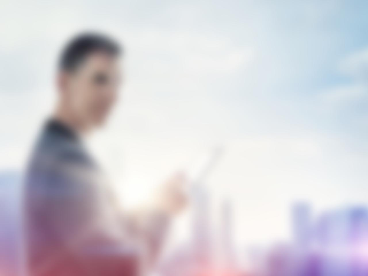 Businessman with digital tablet and blurred city on horizon