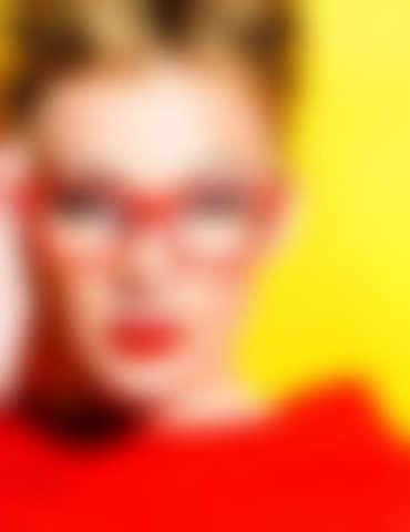 Close-up portrait of a stunning female model in red dress and elegant spectacles posing over yellow background. Beauty, fashion, optics.