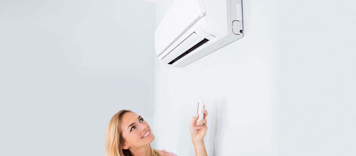 Woman Operating Air Conditioner With Remote