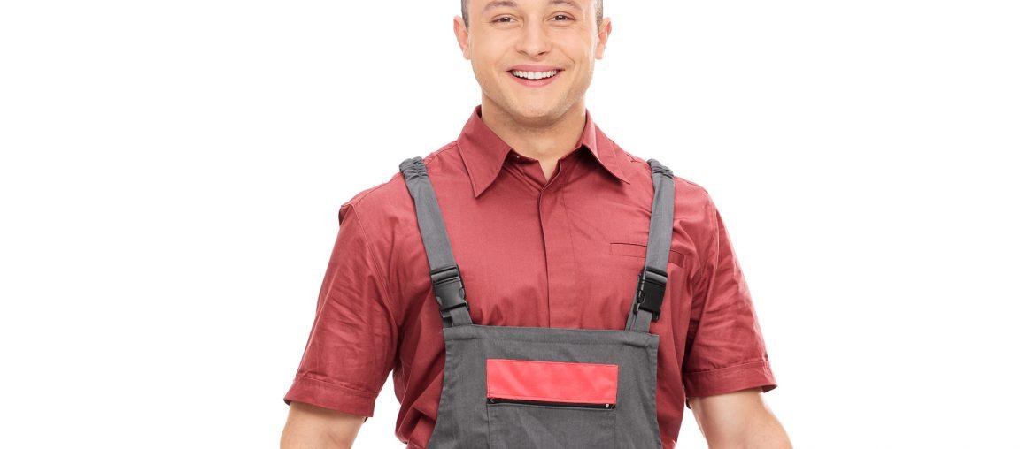 Young joyful mechanic in a gray jumpsuit