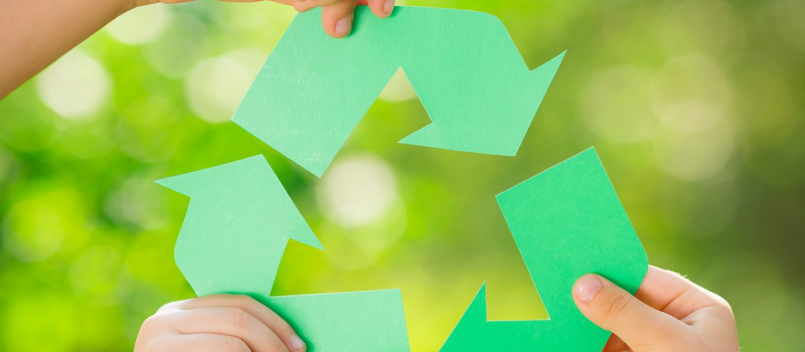 Paper RECYCLE sign in children`s hands