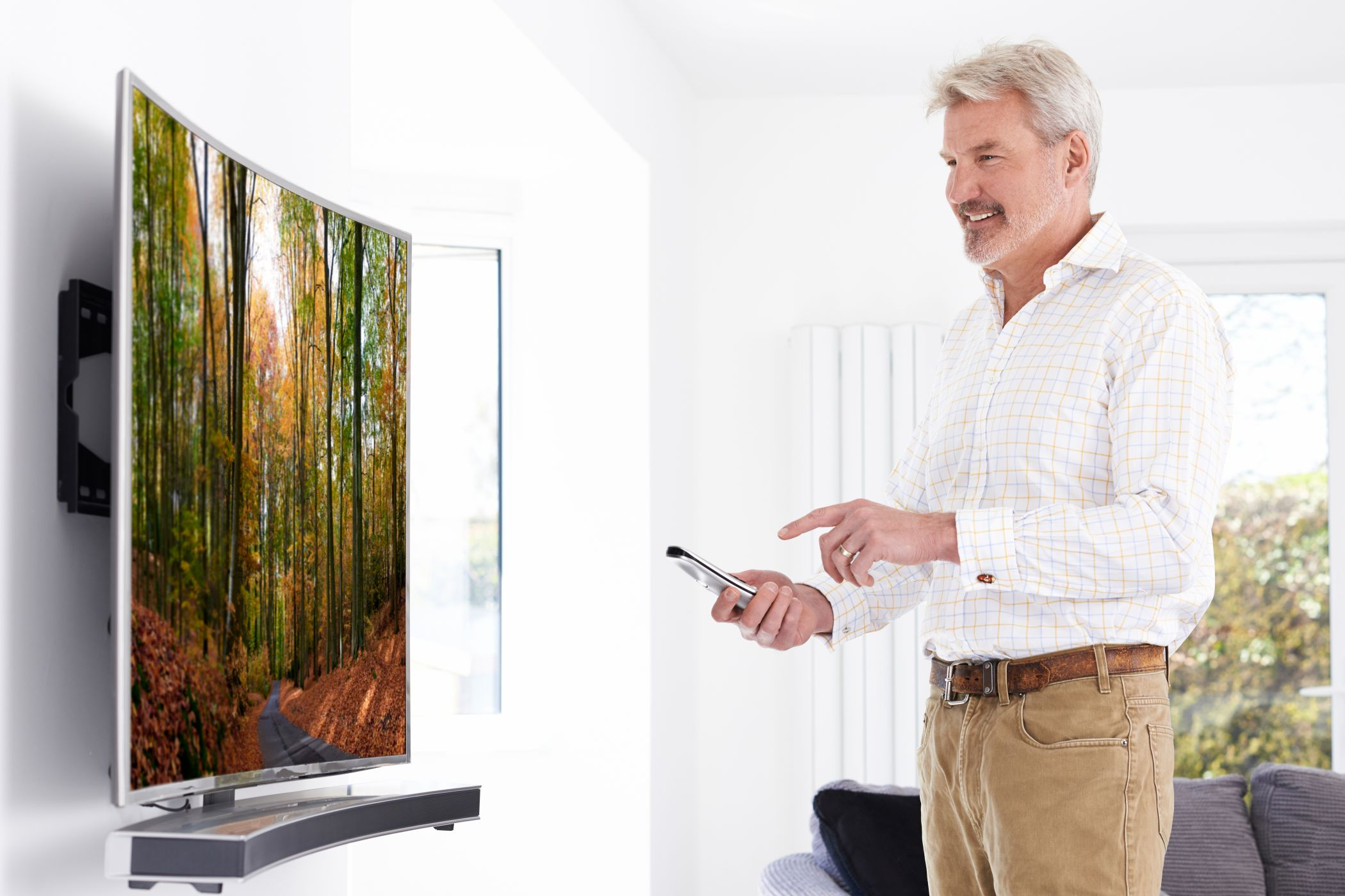 Mature Man With New Curved Screen Television At Home