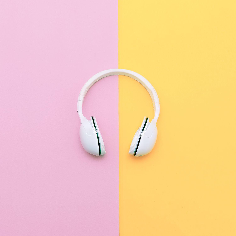 Fashion white headphones on vanilla background. Urban summer time