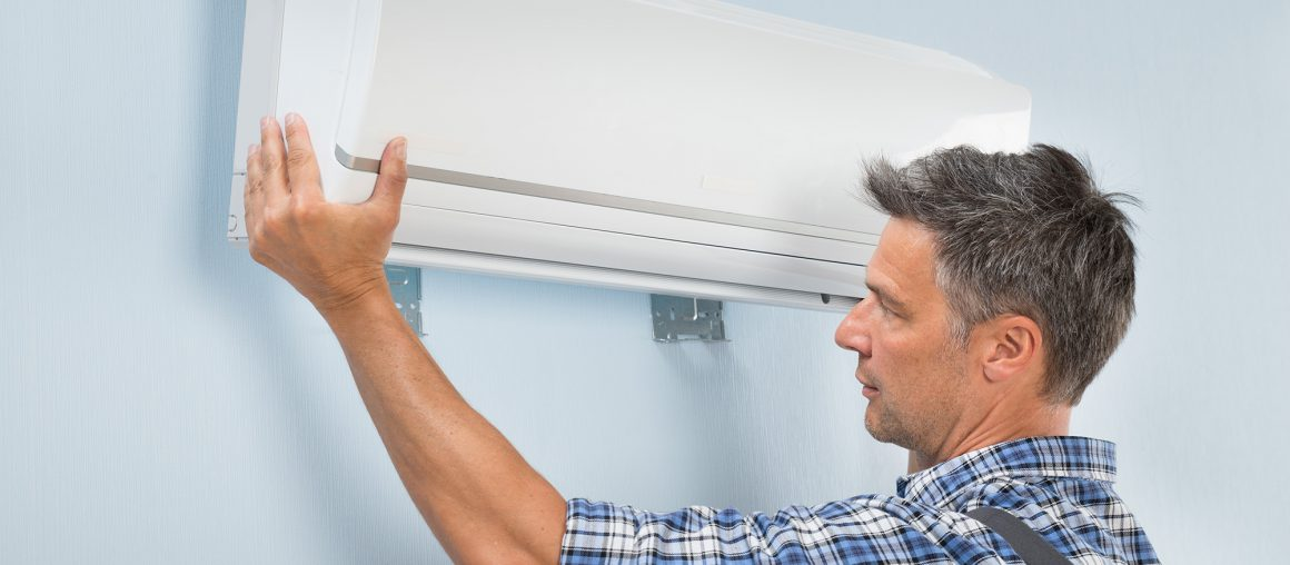 Portrait Of A Mid-adult Male Technician Fixing Air Conditioner On Wall