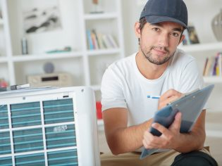 Man with clipboard next to air conditioning unit