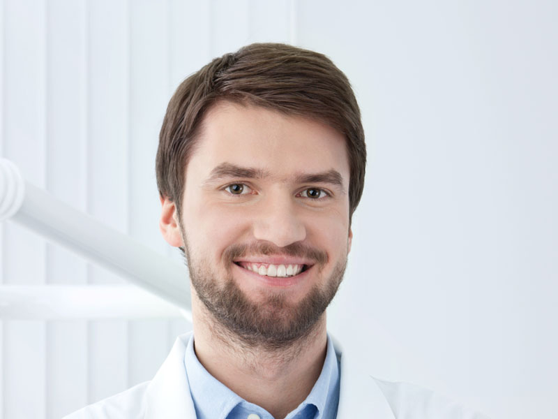 Smiley dentist welcomes the patient